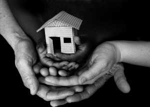 Parent and child hands clasped together, supporting a tiny cardboard house
